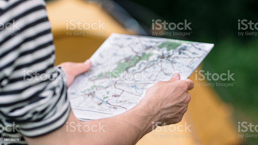 Tourist reading geographic map choosing best way stock photo