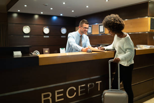 Tourist register in hotel Female tourist arriving in hotel, completing documents. checkout stock pictures, royalty-free photos & images