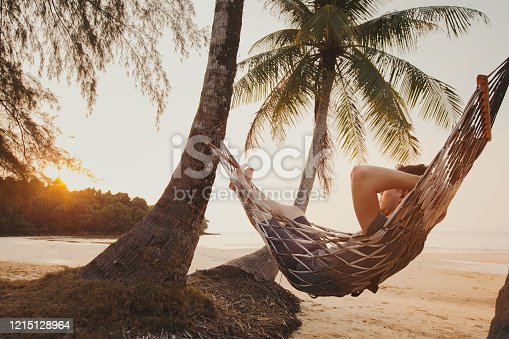 817409212 istock photo tourist relaxing in hammock on tropical beach 1215128964