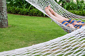 Close up shot female tourist relaxing on rope hammock swing