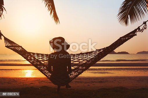 817409212 istock photo tourist relaxing on the beach in hammock, vacation travel 881592374