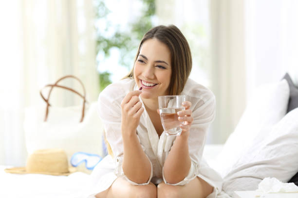 Tourist relieving disease symptoms taking a pill Happy tourist relieving disease symptoms taking a painkiller pill sitting on a bed of an hotel room on summer vacations woman taking pills stock pictures, royalty-free photos & images