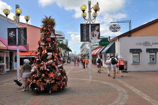 A group of tourist stream through the shopping area in Heritage Quay on their way back to their ships in St, John's, Antigua. AS you can see, while it is early in January, there is still a christmas tree decorated for the season.