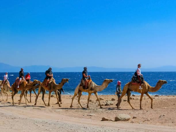 Tourist reitet Kamel am Strand mit Hilfe von ägyptischen Mann – Foto