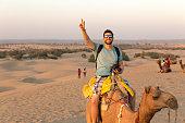 Tourist riding camel in Desert