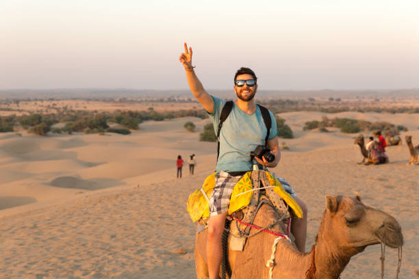 Tourist riding camel in Desert Tourist riding camel in Desert explorer stock pictures, royalty-free photos & images