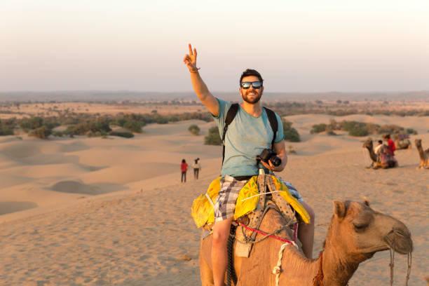 Turista montando en camello en Desert - foto de stock