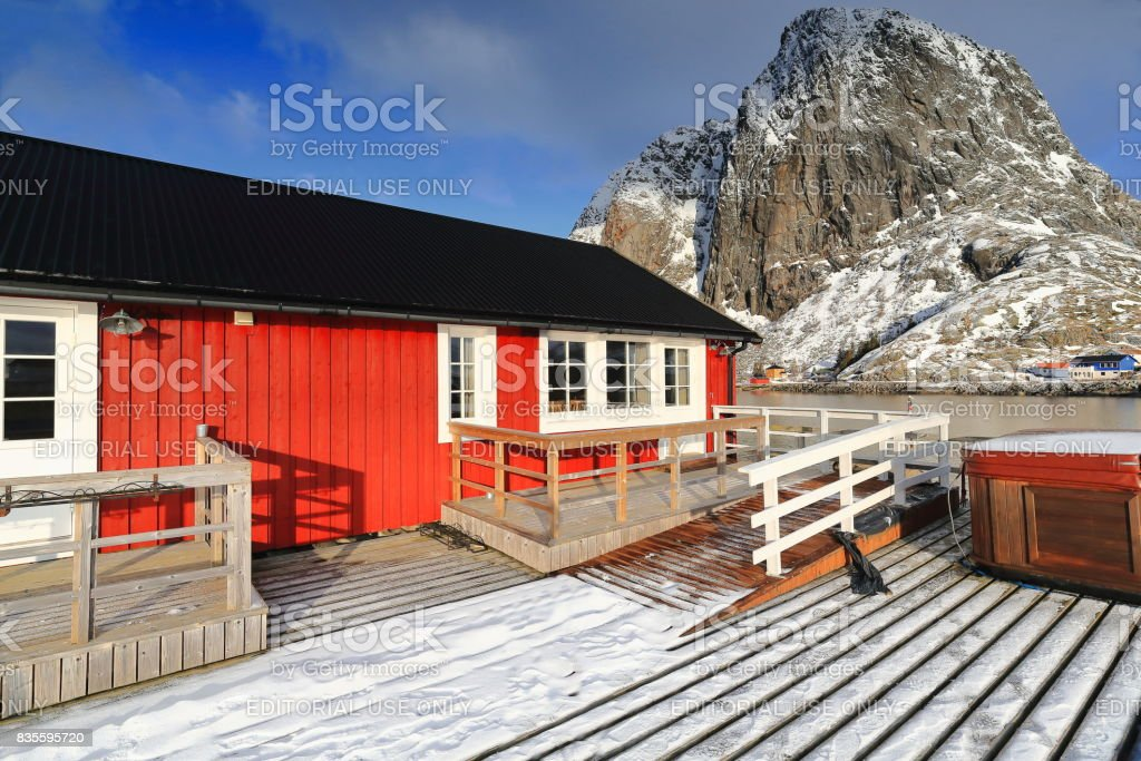 Tourist rorbuer-traditional fishing cottages-Festhaeltinden mount across the fjord. Hamnoy-Reine-Moskenesoya-Lofoten-Norway. 0245 stock photo
