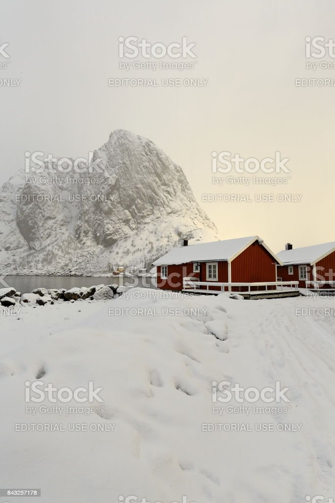 Tourist rorbuer-traditional fishing cottages-Festhaeltinden mounts across the fjord. Hamnoy-Reine-Moskenesoya-Lofoten-Norway. 0354 stock photo