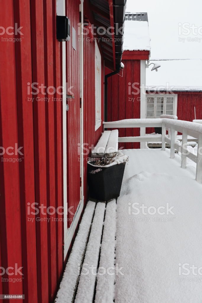 Tourist rorbuer-traditional seasonal cottages-gangplank and bench under snowfall. Hamnoy-Reine-Moskenesoya-Lofoten-Norway. 0384-2 stock photo