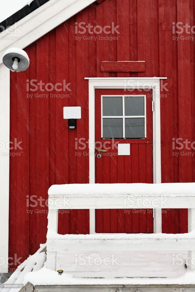 Tourist rorbuer-traditional seasonal cottages-gangplank with fence under snowfall. Hamnoy-Reine-Moskenesoya-Lofoten-Norway. 0385-2 stock photo