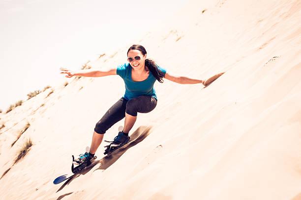 tourist sandboarding in the desert stock photo