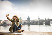 A beautiful young tourist girl using phone next to the Vltava river in Prague, taking selfies