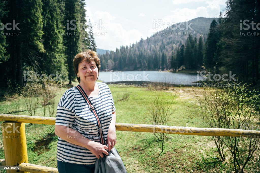 Tourist senior beautiful woman standing on the bank of the mountain lake surrounded by forest, enjoying silence and harmony of nature stock photo