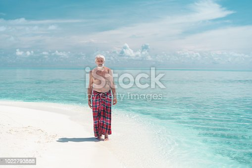 Senior man, tourists in sarong, ready for performing a Karate kata on Sand Bank near Maffushi Island on Maldives at water edge and shallow water, on cloudy day.  It is tropical paradise island, one of places for visiting from Maafushi Island on day tour. It is dark rainy day the beginning of rain season. Maafushi is Kaafu Atoll, central point for traveling around the sandy islands, resorts.