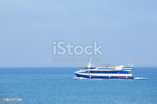 Tourist ship sailing on blue sea near Salou, Catalonia, Spain. Copy space.
