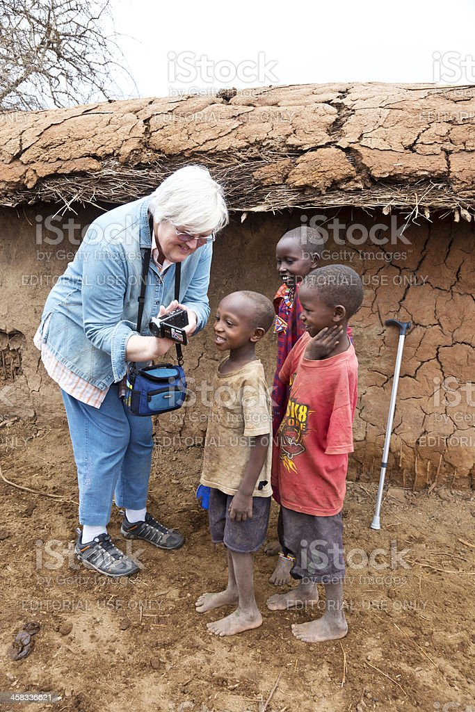 Tourist showing video to children in Maasai village stock photo