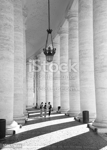 Rome, Italy, October 2017. Tourists enjoying a relaxing moment around the travertine pillars at the Saint Peter's basilica in Rome, Italy.
