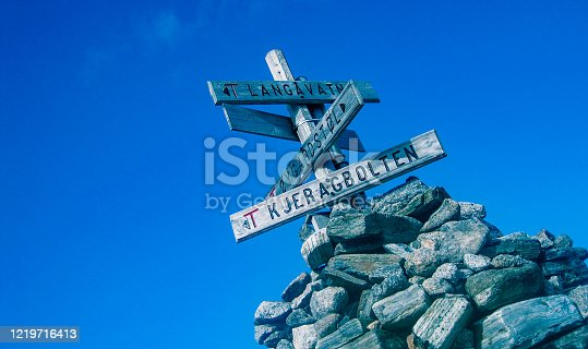 tourist sign at Kjeragbolten Norway hike with blue sky stones