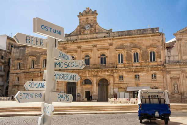 Touristischer Wegweiser mit Entfernungen und im Hintergrund die Gemeinde Ostuni (Italien) – Foto