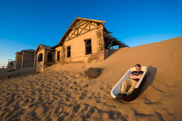 Tourist sits in a bathtub in Kolmanskop ghost town, Namibia stock photo