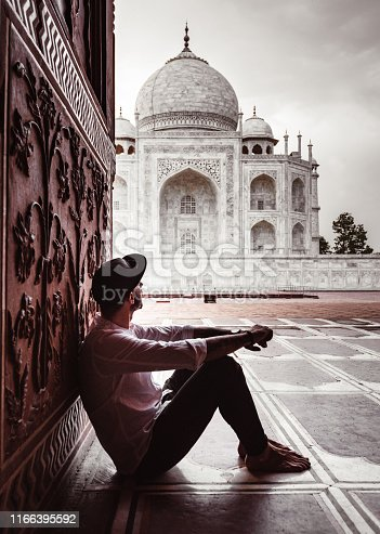 tourist sitting at the entrance of taj mahal in agra
