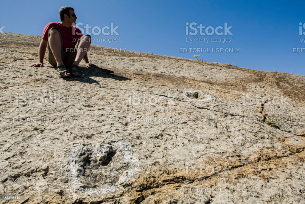 Tourist sitting close to several dinosaur fossil trackways, Sesimbra, Portugal stock photo