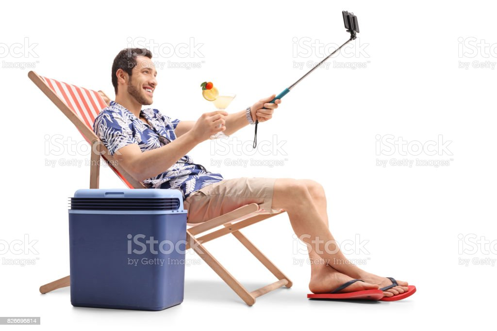 Tourist sitting in a deck chair and taking a selfie stock photo