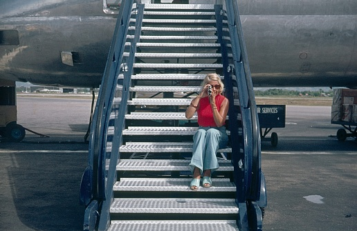 Barbados, Lesser Antilles, 1976. Tourist sitting on a plane gangway filming with an 8mm camera.