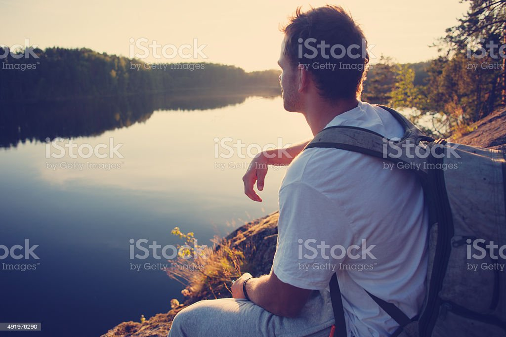 Tourist sitting on the cliff above the lake stock photo