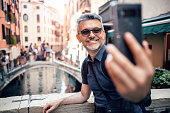 Happy handsome senior bearded man smiling while taking selfie picture with mobile phone and wearing eyeglasses outdoors