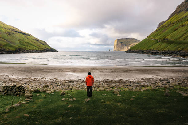 Tourist standing at the beach in Tjornuvik in the Faroe Islands, Denmark stock photo