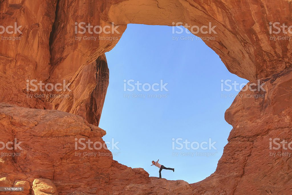 Tourist standing in a natural arch stock photo