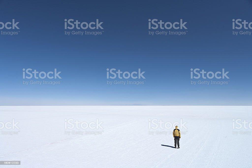 Tourist standing on Salar de Uyuni, Altiplano Bolivia royalty-free stock photo