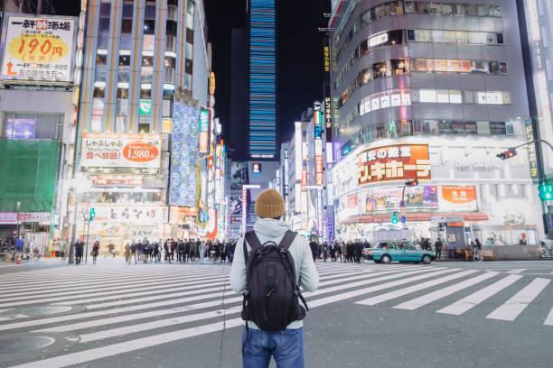 Um turista em pé na rua urbana em Kabukicho, Shinjyuku à noite - foto de acervo