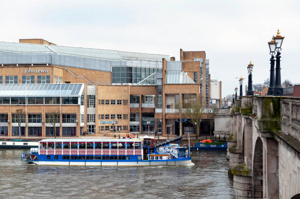tourist steam boat cruising along the river thames passing john lewis shopping mall and kingston bridge in kingston upon thames, england - john lewis стоковые фото и изображения