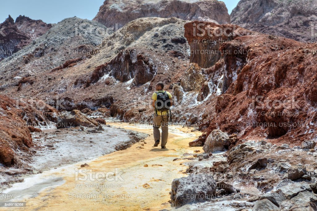 Tourist strolls through the valley of salt, Hormuz Island, Iran. stock photo