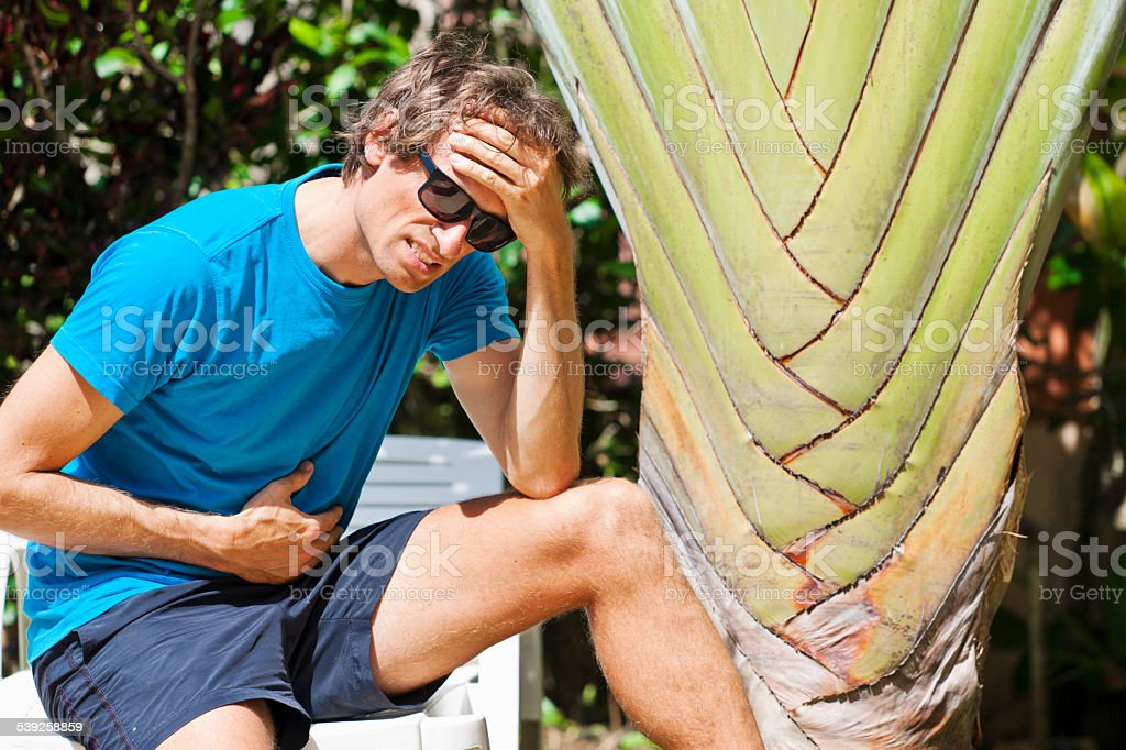 Tourist suffering under fever and stomach ache maybe having Malaria stock photo