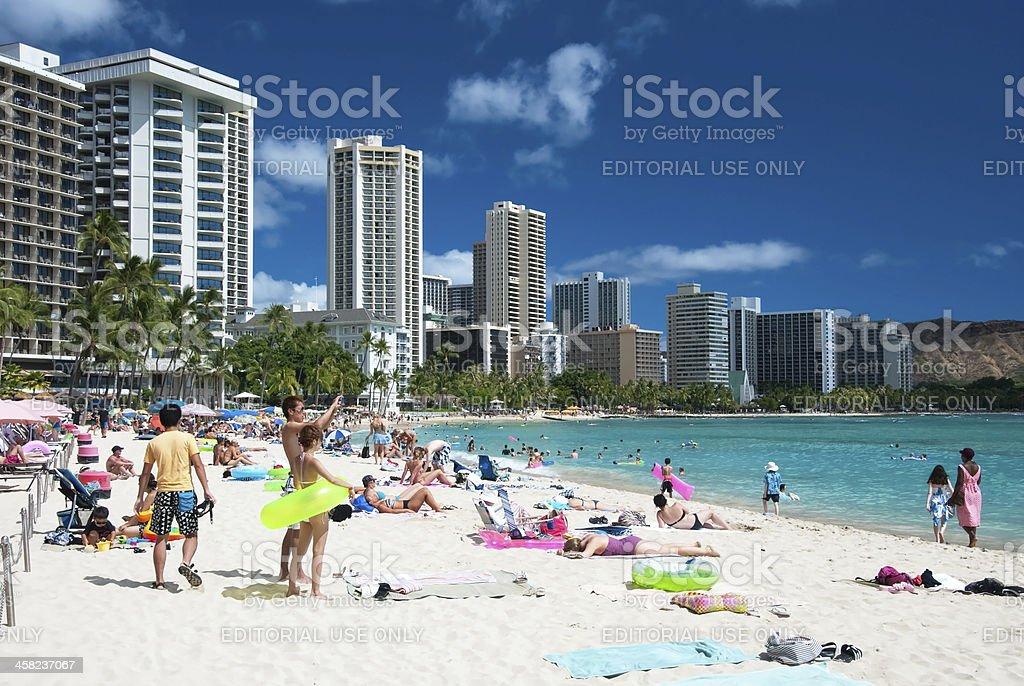 Tourist sunbathing and surfing on the Waikiki beach in Hawaii. stock photo