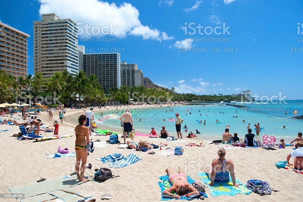 Tourist Sunbathing And Surfing On Waikiki Beach Hawaii Oahu