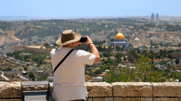 Tourist takes a photo of Jerusalem Old City view Jerusalem, Israel - May 25, 2017: Tourist takes a photo of Jerusalem Old City view. Mount Scopus is a famous Holy Land place and it has a fantastic view to the Old Jerusalem muslim quarter stock pictures, royalty-free photos & images