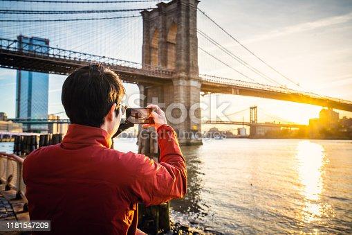 Tourist taking a photo of Brooklyn Bridge at sunrise.