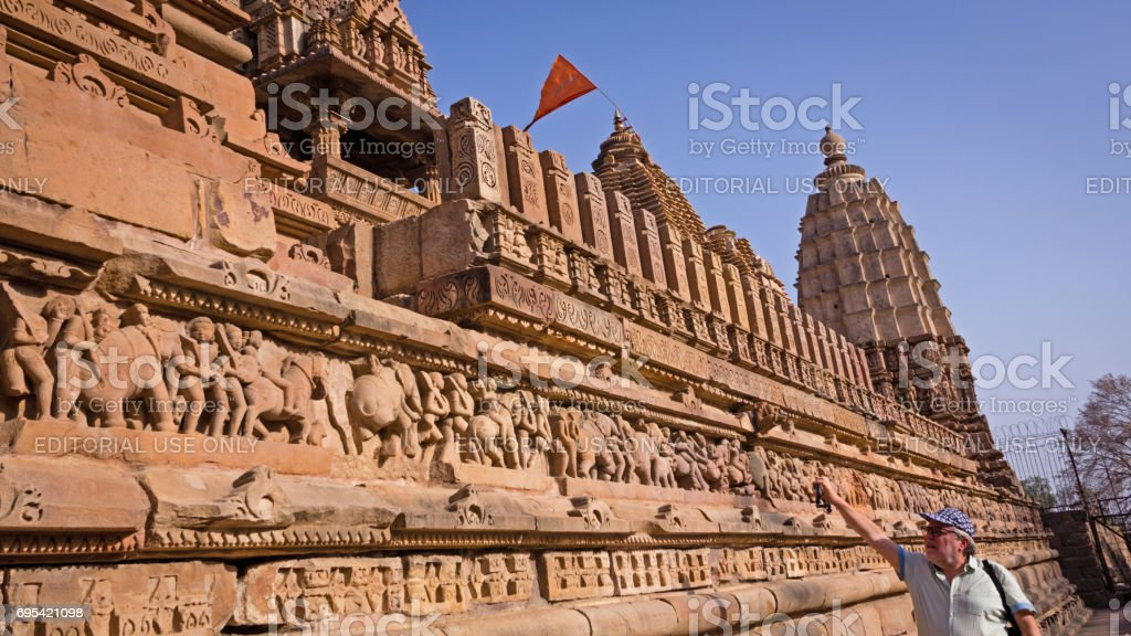 A tourist taking a picture of Lakshmana Temple's base in the Western Group of Temples stock photo