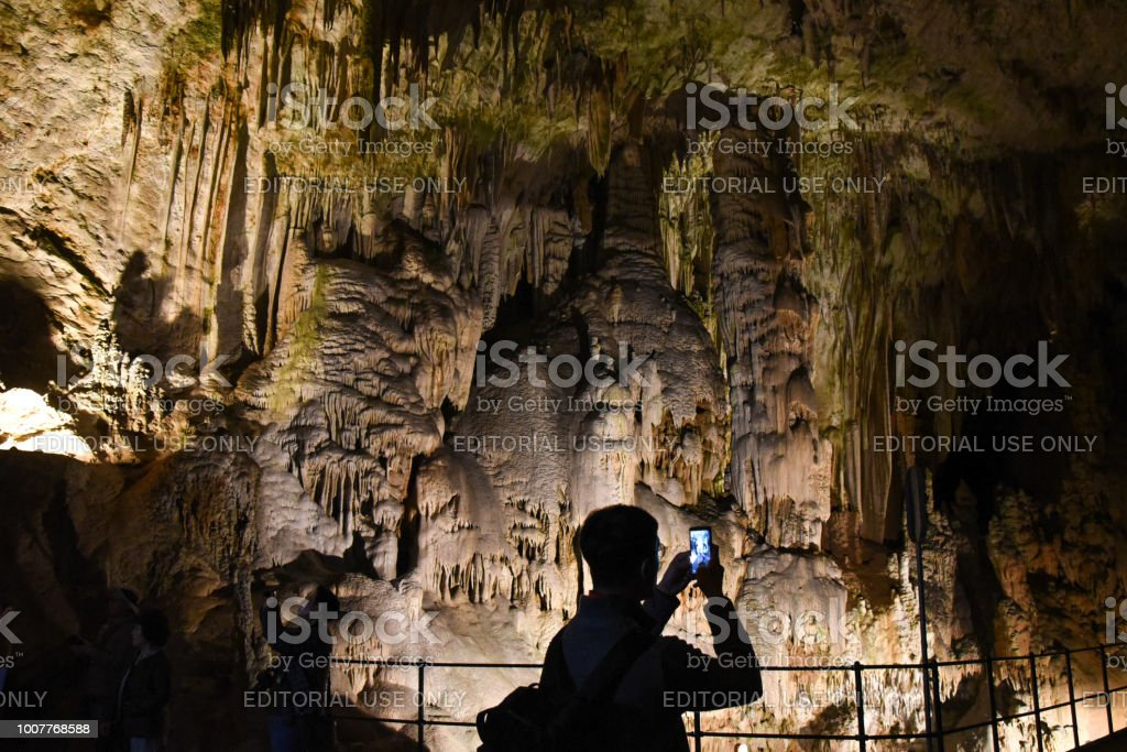 Tourist taking a picture with his phone inside a cave in Slovenia stock photo