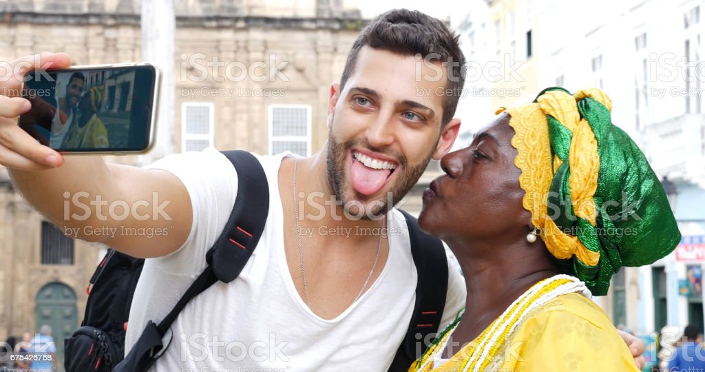 Tourist taking a selfie with a Baiana in the old colonial district of Salvador, Brazil stock photo