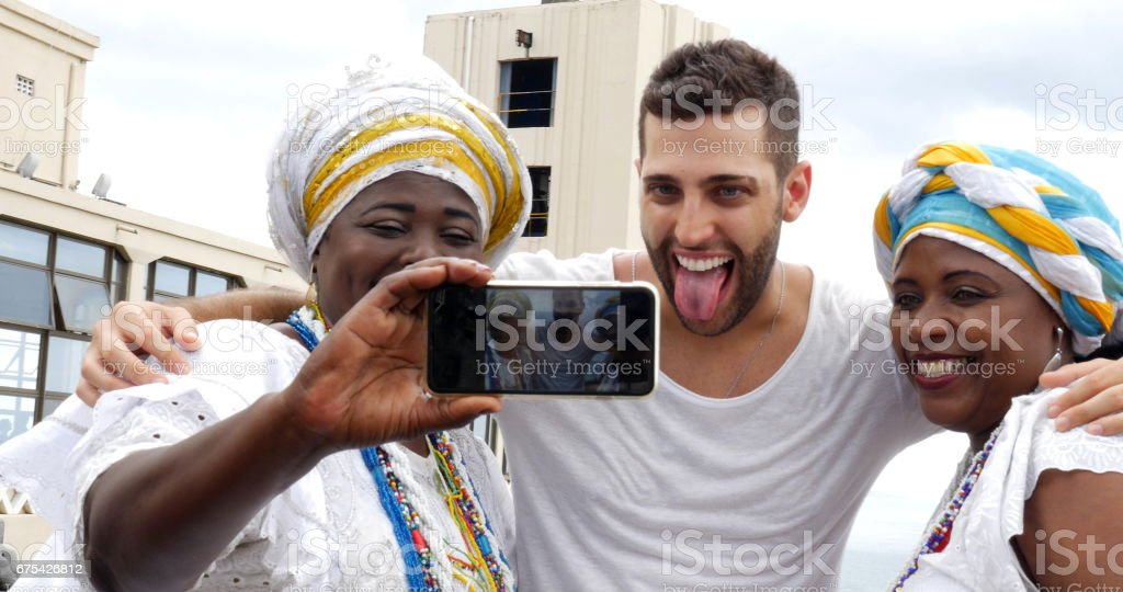 Tourist taking a selfie with tradicional Brazilian Women - Baianas stock photo