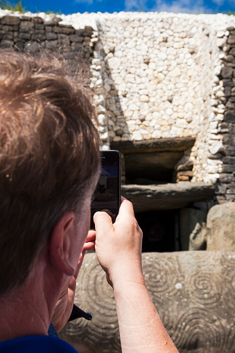 County Meath, Ireland - June 1, 2016. Tourist taking a photo with his smart phone at Newgrange in County Meath, it was built during the Neolithic period, around 3200 BC.