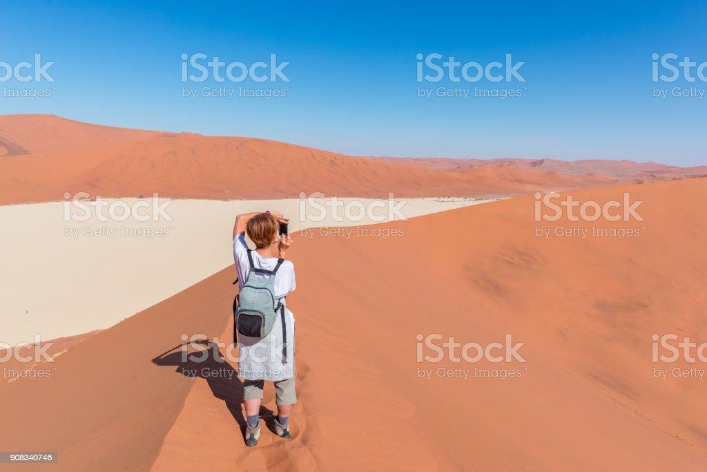 Tourist taking photo at Sossusvlei, Namibia. Scenic sand dunes, Namib desert, Namib Naukluft National Park, travel adventure in Africa. stock photo