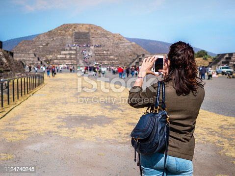 Tourist taking photo of the Pyramid of the Moon at the ancient Aztec city of Teotihuacan near Mexico City, Mexico.