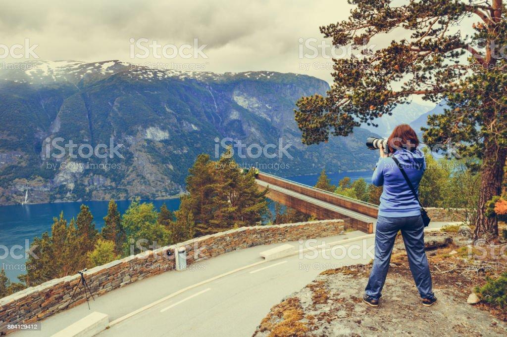 Tourist taking photo from Stegastein viewpoint Norway royalty-free stock photo